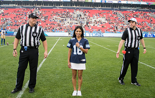 Argos football starting with a coin toss where cheerleader is wearing custom jersey.