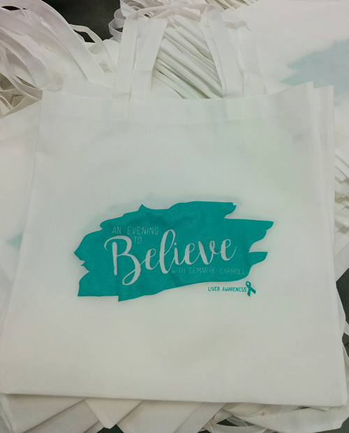 Charitable custom tote bags printed in white with custom design for giveaways.