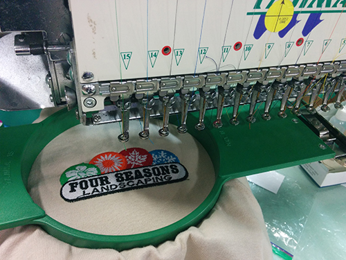 Custom embroidery machine printing client order on embroidered custom shirts.