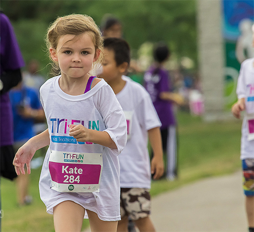 Kids running at the Tri-FUN marathon wearing custom printed t-shirts.
