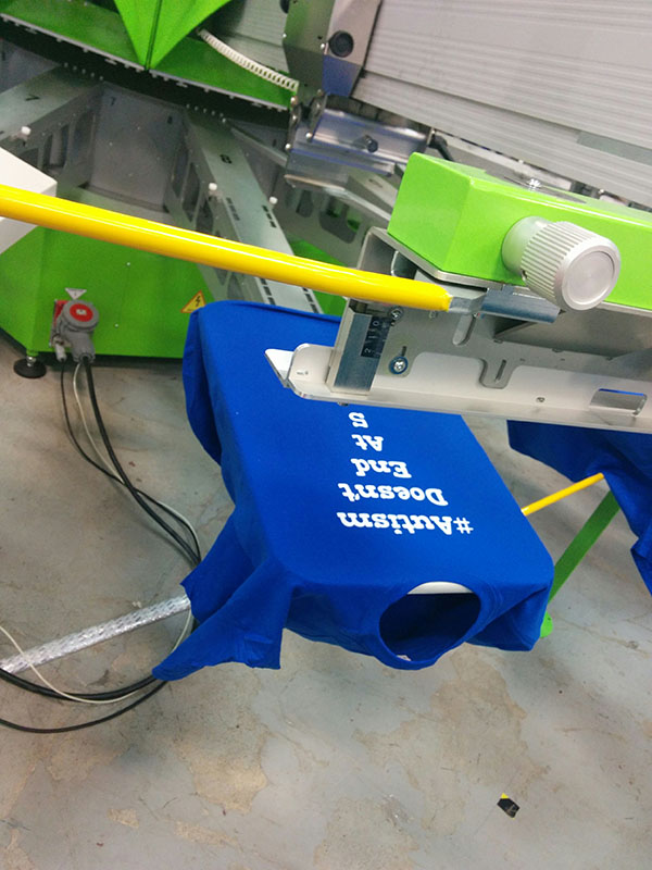 Custom t-shirt printing a custom design with ROQ screen-printing press.