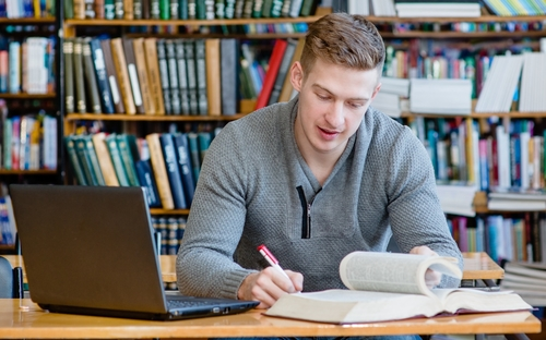Student-Entrepreneur-in-library-with-laptop-and-books-planning-his-own-business-strategy