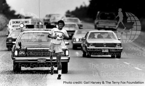 Terry Fox running his Marathon of Hope with vehicles following him during his run.