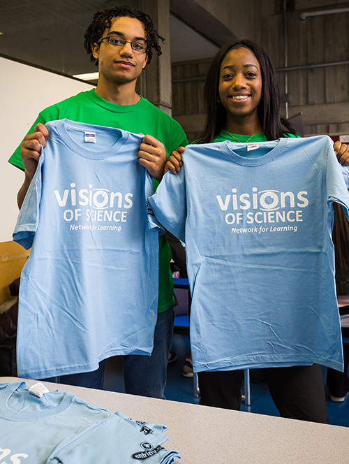 Youth giving away custom printed t-shirts from Vision of Science organization.