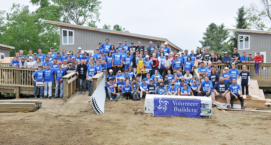 Volunteer builders wearing custom t-shirt with their design at the charity gathering.