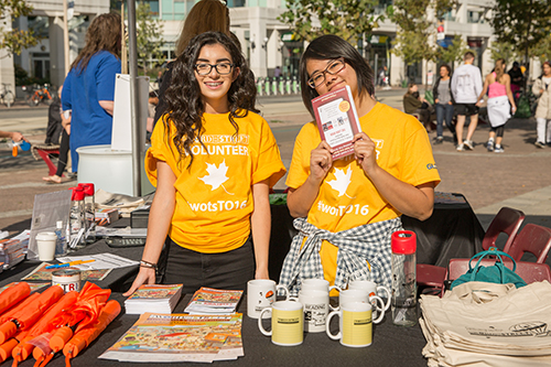 Volunteers at The Word on the Street festival showcasing custom t-shirts, books, custom bags and custom mugs.
