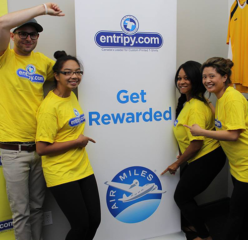 Entripy employees displaying Air Miles Get Rewarded sign with yellow custom t-shirts.