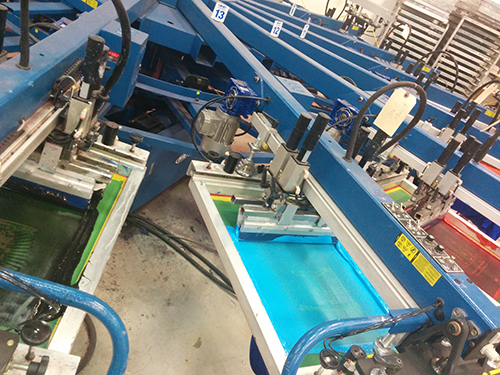Automatic screen-printing machines running a custom t-shirt order.