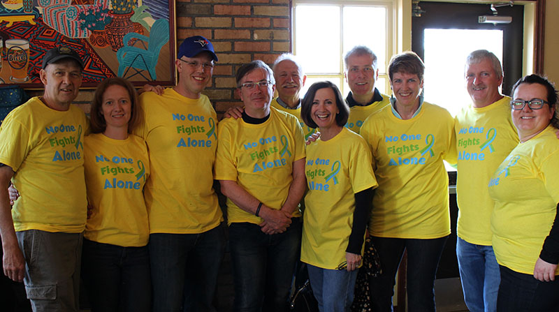 Group of people wearing bright yellow charity custom printed t-shirts.