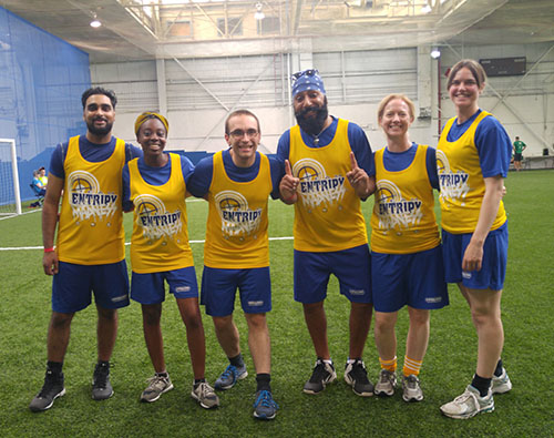 Entripy employees competing at a work event wearing custom jerseys.