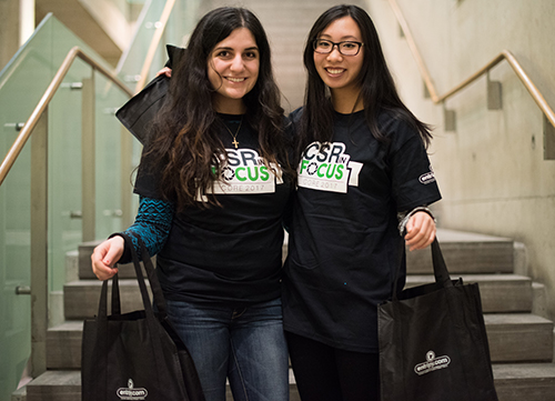 Participants at a charity event wearing custom t-shirts and holding promo giveaways of custom tote bags.