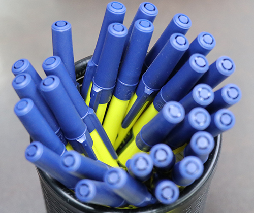 A pack of custom pens made with entripy logo and blue and yellow colours for clients.