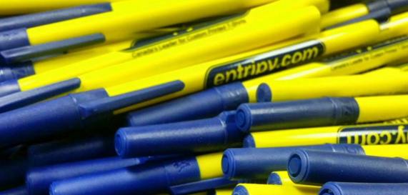 Pile of yellow and blue custom pens that are branded with Entripy's logo as custom promotional product.