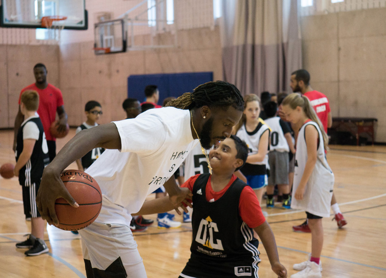 Toronto raptors playing basketball at the kids camp wearing white custom t-shirts and kids wearing custom jerseys.