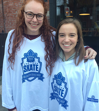 Volunteers at Easter Seals Skate wearing white custom jerseys of Toronto Maple Leafs.