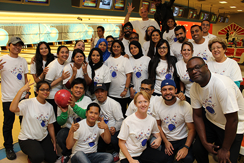 Entripy employees at a bowling event wearing custom t-shirts with Entripy logo and personalized with names.