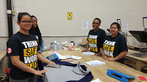 Entripy employees wearing customized t-shirts for Health & Safety week while doing heat transfer printing.