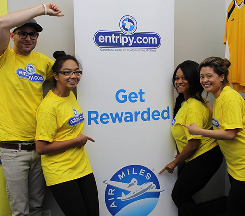 Entripy employees displaying AirMiles and Entripy banner for customer visiting main location to pick up custom apparel orders.