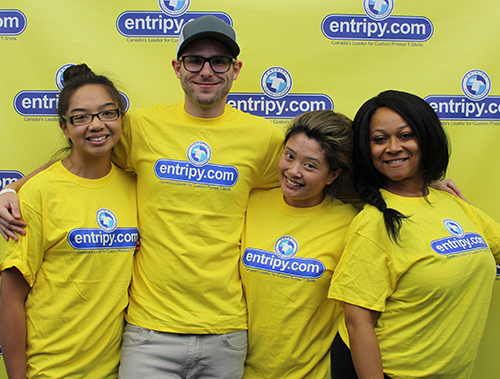 Entripy employees wearing yellow custom printed t-shirts.