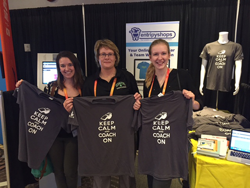 Customers holding black custom t-shirts at a trade show for EntripyShops.