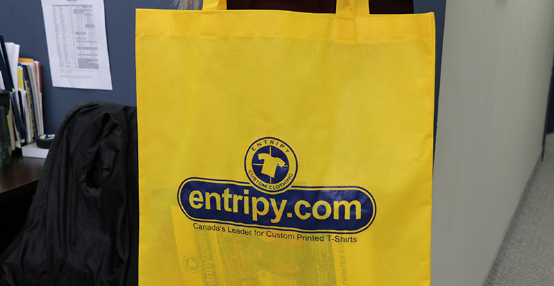 Entripy's yellow custom tote bag used as a conference swag bag at tradeshows.