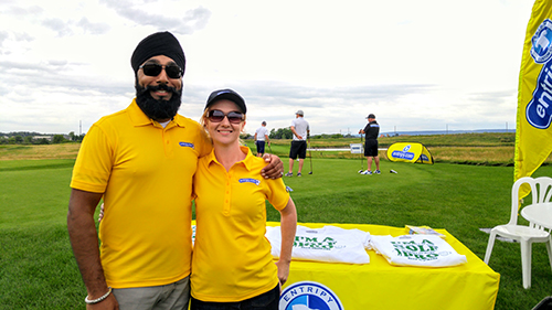 Entripy employees wearing yellow custom golf shirts for personalized uniforms at an event.