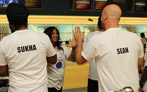 Entripy's employees wearing white custom t-shirts at bowling with their names personalized on the back.