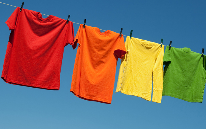 Colourful custom t-shirts hanging outside to dry for preserving the colour and custom logo.