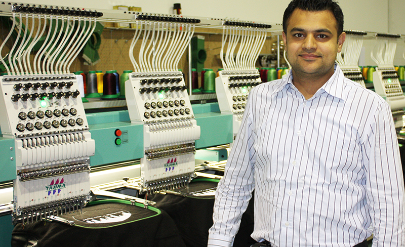 Entripy's CEO, Jas Brar, showcasing the embroidered machines used for custom clothing.