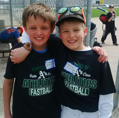Youth sports players in their custom baseball t-shirt and custom cap representing their team.