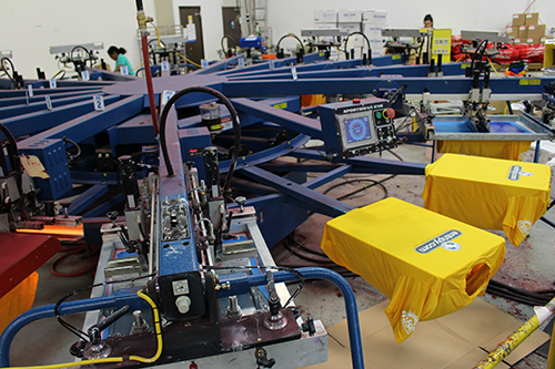 Custom printed t-shirts on screen-printing machines with custom logos.