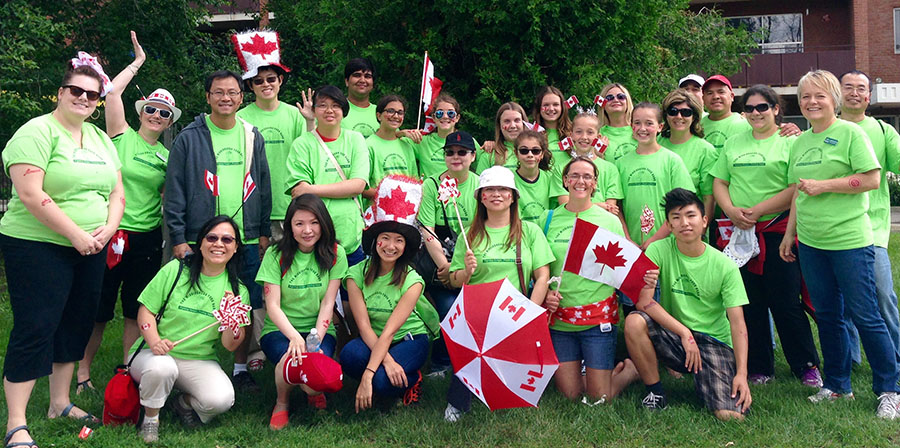 Group of participants displaying their green custom shirts at a charity event for the Mississauga Food Bank.