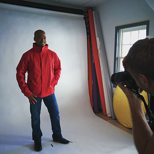 Model posing wearing red zip up custom jacket for a photoshoot.