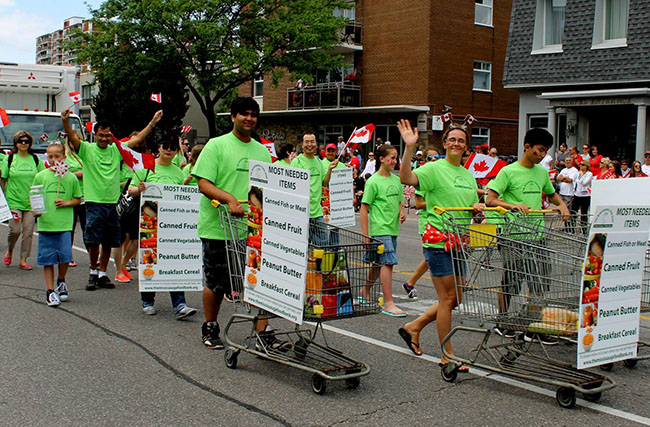 Participants wearing custom clothing and raising community food drives with shopping carts filled with food for the Mississauga Food Bank.