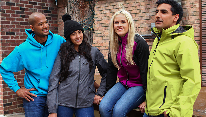 Group of people outdoors wearing custom sweatshirts, custom embroidered jackets and pom pom touque.