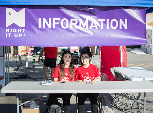 Event information booth with volunteers wearing custom printed t-shirts.