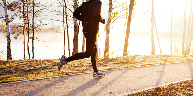 Active individual wearing athletic wear including custom jacket is jogging.
