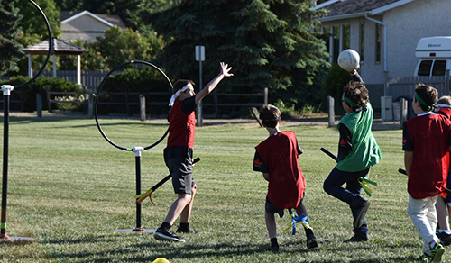 Students playing Quidditch wearing red and green custom jerseys.