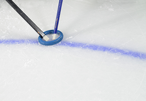 Rubber rings and stick displayed on the ice rink for the Ringette sport.