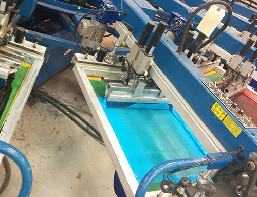 A screen-printing machine printing custom apparel orders with their customized logos.