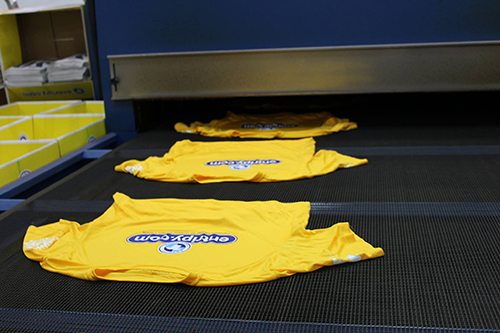 Printing custom t-shirts and putting them through a dryer for the last completing step.