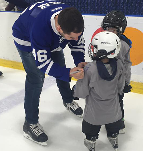Roman Polak from Maple Leafs signing kids custom jerseys at Easter Seals skate.