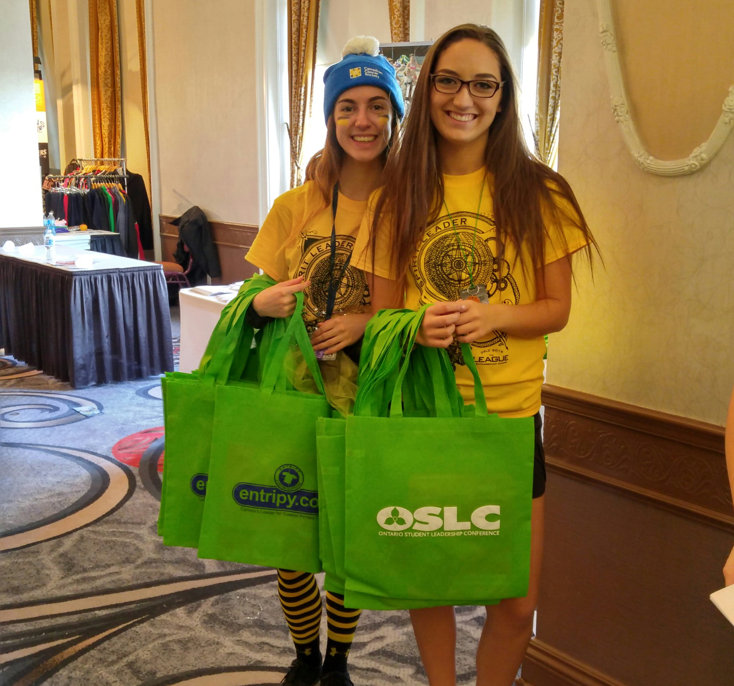 Students wearing custom t-shirts, embroidered toques and displaying custom printed totes.