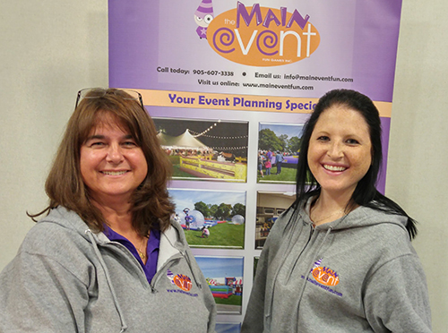 Clients at a trade show wearing their grey custom sweatshirts with their company logo.