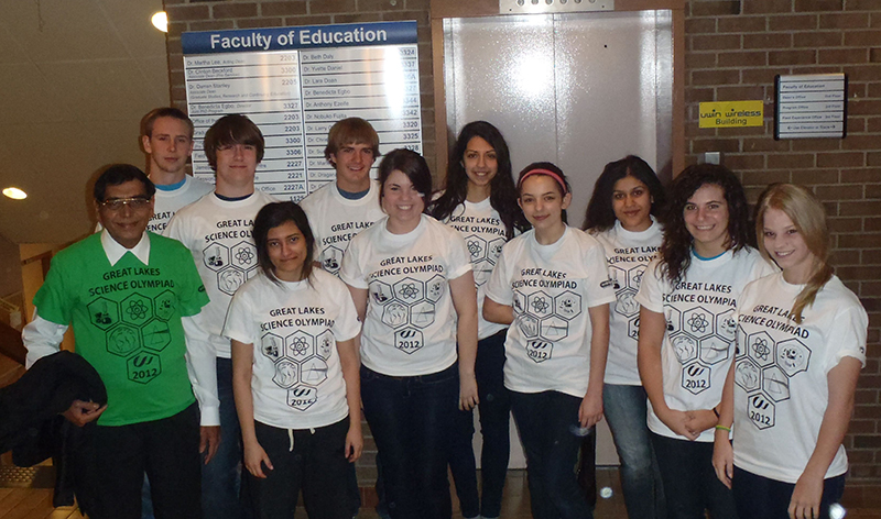 Great Lakes Science team is displaying their white and green custom printed t-shirts at school.