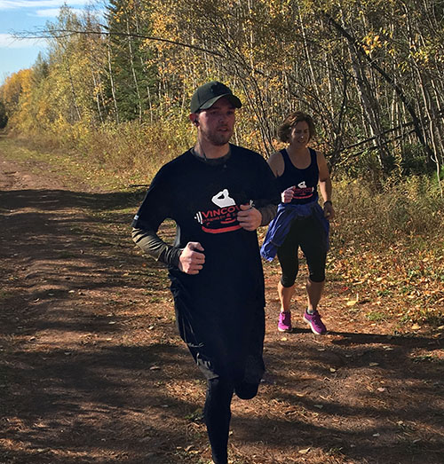 Participant running wearing a black custom t-shirt for a veterans non-profit organization.