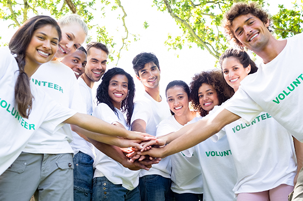 Group of people wearing white custom t-shirts with custom design text of Volunteer on the front.