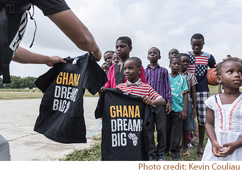 Volunteer members of Giants of Africa organization handing out custom printed t-shirts to children of Ghana.