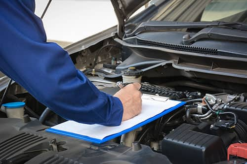 Mechanic writing on a notepad with the hood of the car open.