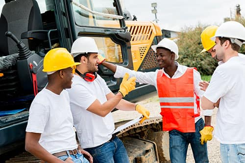 Construction employees discussing work wearing custom t-shirts and high-visibility vests.